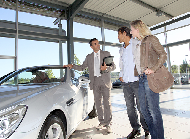 salesman showing a couple a new car