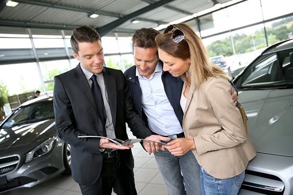 salesman talking to a couple about cars